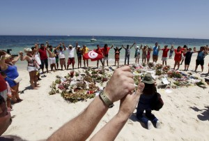 People join hands as they observe a minute's silence in memory of those killed in a recent attack by an Islamist gunman, at a beach in Sousse, Tunisia July 3, 2015. Tunisian authorities were on Thursday hunting further suspects in the Sousse hotel attack identified by officials as part of a group trained in a Libyan jihadist camp alongside gunmen who carried out a massacre at a Tunis museum. Thirty-eight foreigners, most British holidaymakers, were killed in last Friday's attack before the gunman was shot by police. REUTERS/Anis Mili - RTX1IWIY