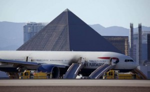 Casinos along the Las Vegas Strip can be seen behind a plane that caught fire at McCarren International Airport, Tuesday, Sept. 8, 2015, in Las Vegas. An engine on the British Airways plane caught fire before takeoff. (AP Photo/John Locher)