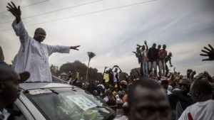 TOPSHOT - Adama Barrow, the flag-bearer of the coalition of the seven opposition political parties in Gambia, greets supporters from the roof of his car at a gathering in the buffer Zone district of Talinding on November 29, 2016 on the last day of the presidential campaign in Gambia. Gambian opposition leader Adama Barrow said on November 29 he believed his coalition would sweep the presidential election in two days time following unprecedented rallies nationwide, and urged President Yahya Jammeh to go peacefully if he loses power. The businessman emerged from obscurity to become the flagbearer of all The Gambia's opposition parties bar one after mass arrests of supporters from the largest anti-government grouping in April  / AFP / MARCO LONGARI        (Photo credit should read MARCO LONGARI/AFP/Getty Images)