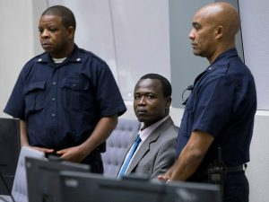Dominic Ongwen, a senior commander in the Lord's Resistance Army, whose fugitive leader Kony is one of the world's most-wanted war crimes suspects, is flanked by two security guards as he sits in the court room of the International Court in The Hague, Netherlands EPA